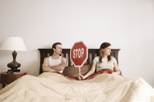Couple holding stop sign in bed